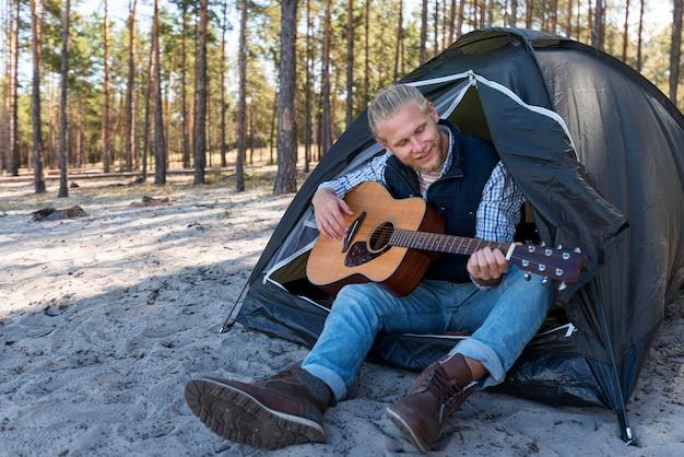 Mężczyzna gra na gitarze akustycznej i siedzi w swoim namiocie