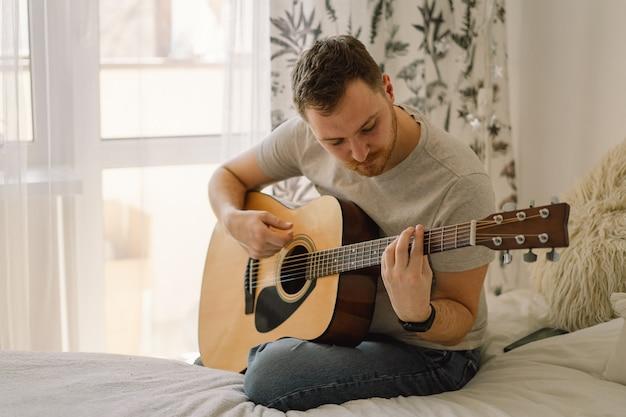 Mężczyzna gra na gitarze akustycznej w pokoju w domu