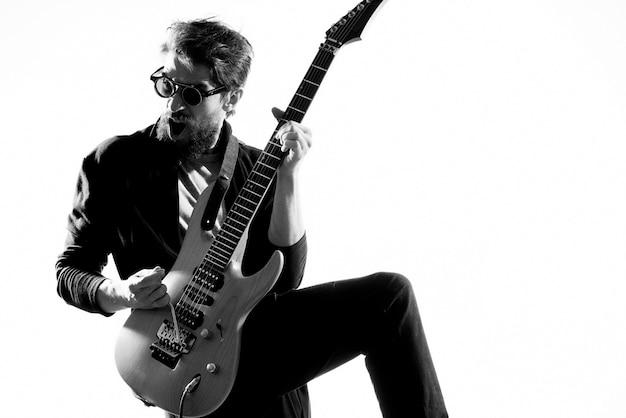 Mężczyzna gra na gitarze elektrycznej, czarno-białe zdjęcie