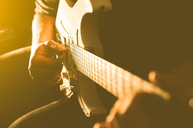 Mężczyzna gra na gitarze elektrycznej w cieniu. zdjęcie instrumentu muzycznego. muzyk w centrum uwagi. kreatywny styl z jasnymi cieniami.
