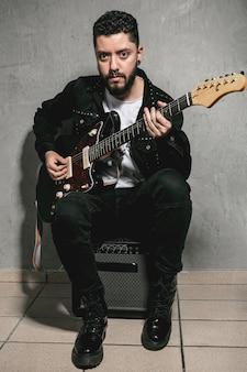 Mężczyzna gra na gitarze i patrząc na fotografa