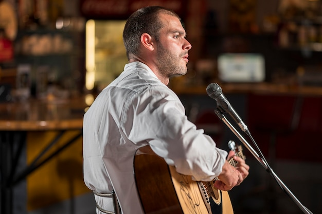 Mężczyzna gra na gitarze i śpiewa na mikrofonie w barze