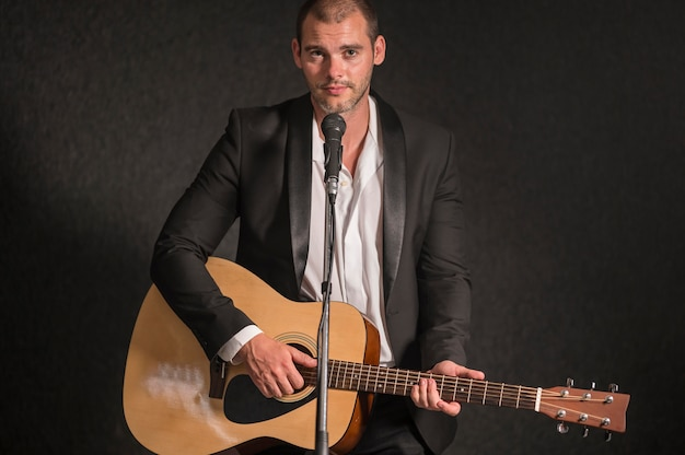 Mężczyzna gra na gitarze i śpiewa na mikrofonie