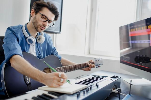Mężczyzna gra na gitarze i tworzy elektroniczną ścieżkę dźwiękową