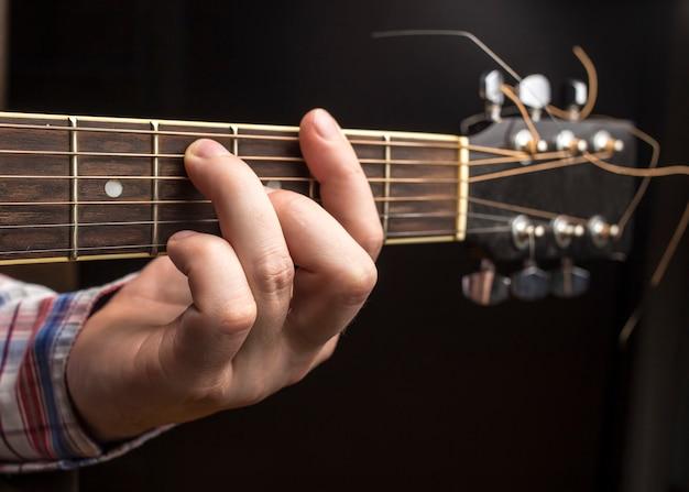 Mężczyzna gra na gitarze, kciuki zmieniają akordy