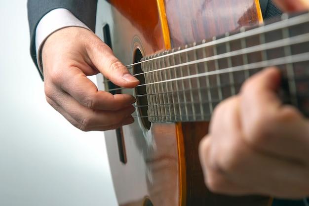 Mężczyzna gra na gitarze klasycznej na białym tle. twórczość muzyczna. strunowy instrument muzyczny
