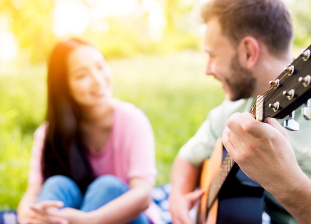 Mężczyzna gra na gitarze na pikniku