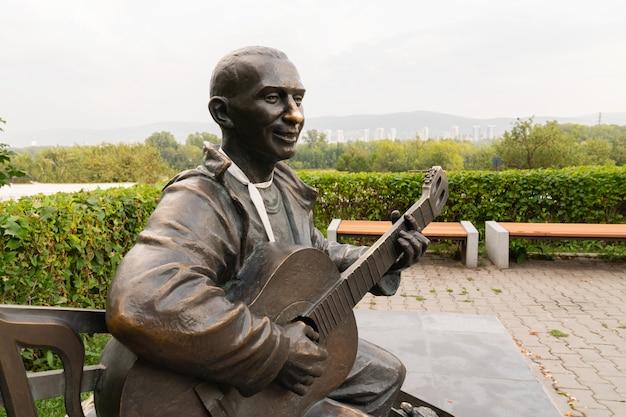 Mężczyzna gra na gitarze, pomnik ulicy, punkt orientacyjny, miejsca dla turystów i miłośników