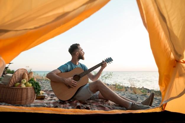 Mężczyzna gra na gitarze przed namiotem