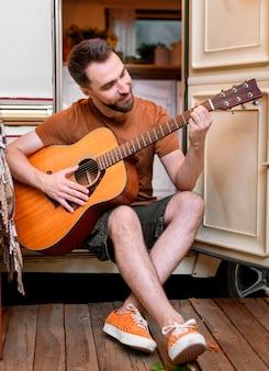 Mężczyzna gra na gitarze przed swoją furgonetką