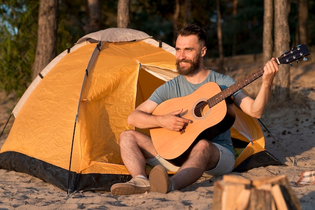 Mężczyzna gra na gitarze przy namiocie