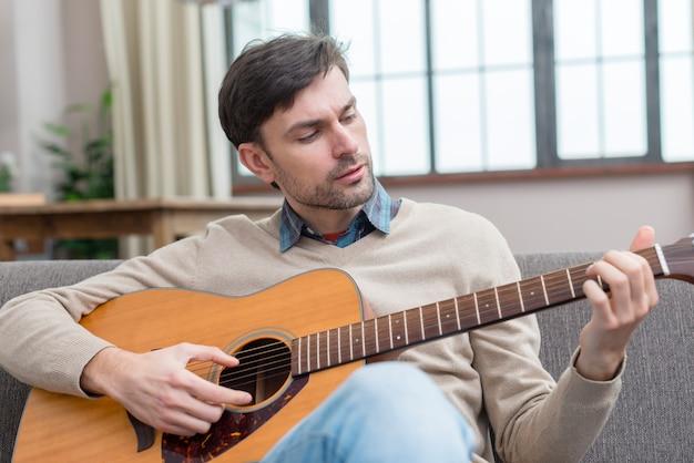 Mężczyzna gra na gitarze średni strzał