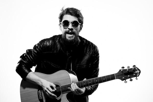 Mężczyzna gra na gitarze w czarnej skórzanej kurtce z okularami przeciwsłonecznymi na jasnej przestrzeni.