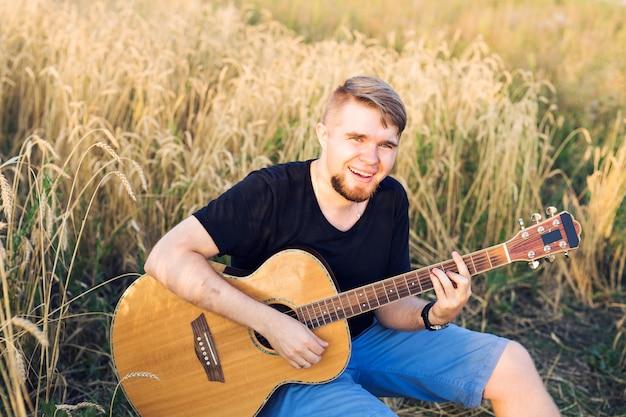 Mężczyzna gra na gitarze w polu trawy w dzień relaksu ze światłem słonecznym