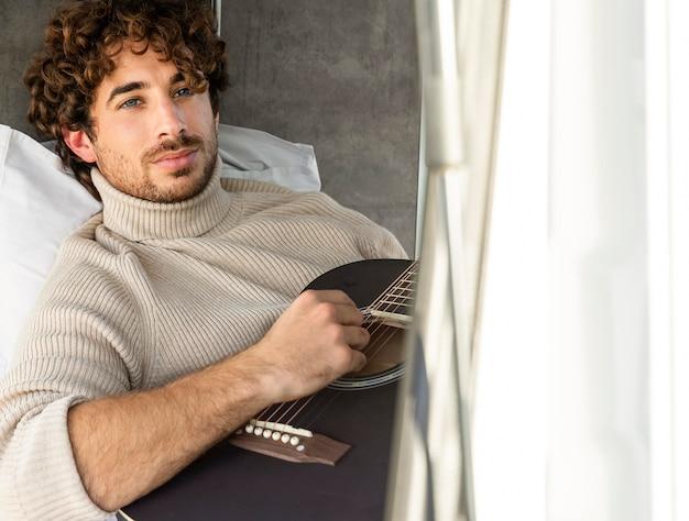 Mężczyzna gra na gitarze z samochodu podczas podróży z miejsca na kopię