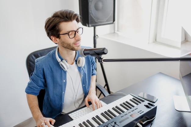 Mężczyzna gra na pianinie i śpiewa w studio