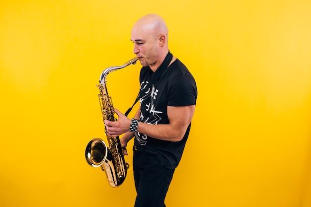 Mężczyzna gra na saksofonie na żółtej ścianie