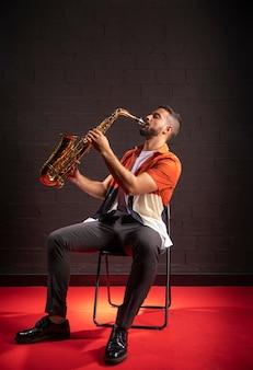 Mężczyzna gra na saksofonie siedząc na krześle