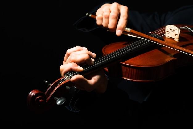Mężczyzna gra na skrzypcach na czarnym tle