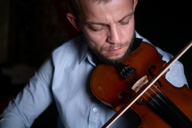 Mężczyzna gra na skrzypcach z bliska.