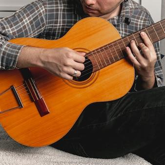 Mężczyzna gra na starej gitarze akustycznej
