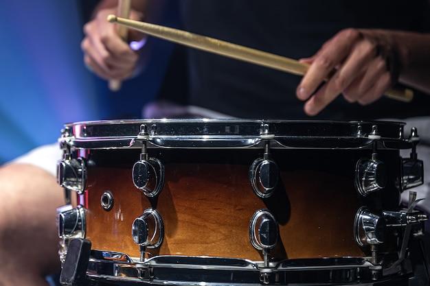 Mężczyzna gra pałkami na bębnie, perkusista gra na instrumencie perkusyjnym, zbliżenie.