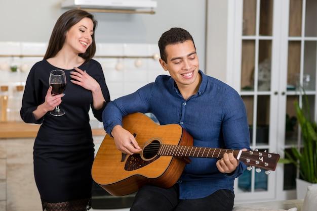 Mężczyzna gra piosenkę na gitarze dla swojej dziewczyny