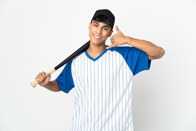 Mężczyzna gra w baseball nad odizolowaną białą ścianą, czyniąc gest telefonu. oddzwoń do mnie znak