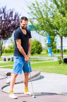 Mężczyzna gra w mini golfa
