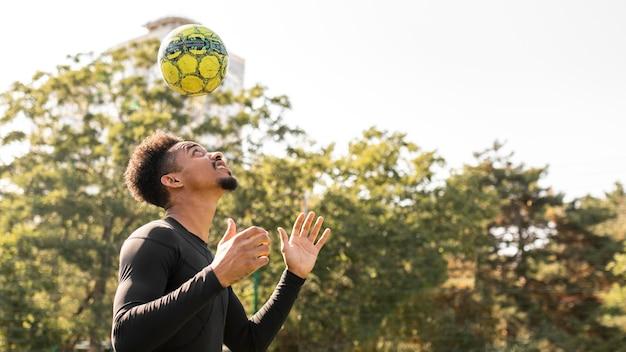 Mężczyzna gra w piłkę nożną z miejsca na kopię