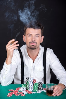 Mężczyzna gra w pokera w kasynie i pali.