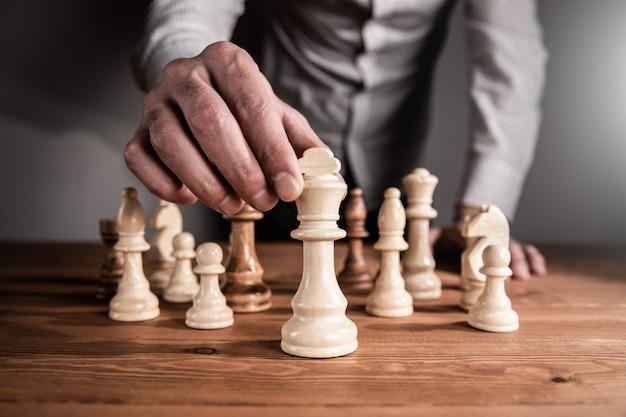 Mężczyzna gra w szachy na ciemnej ścianie