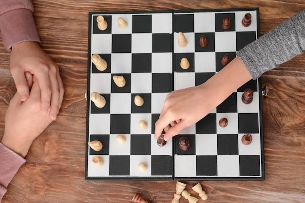 Mężczyzna gra w szachy z kobietą na drewnianym stole
