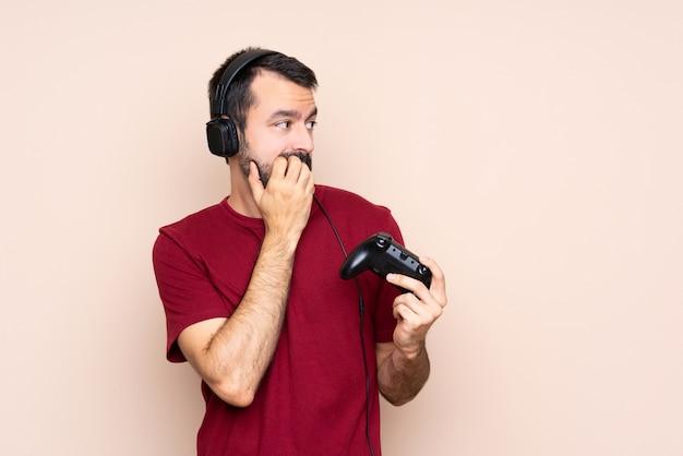 Mężczyzna gra z kontrolerem gier wideo na izolowanej ścianie nerwowy i przestraszony, wkładając ręce do buzi