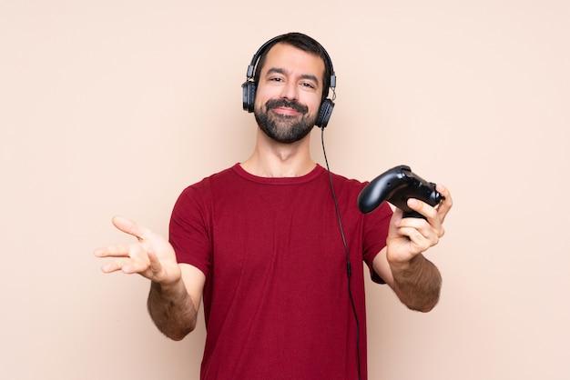 Mężczyzna gra z kontrolerem gier wideo na izolowanej ścianie, prezentując i zapraszając do przyjścia ręką