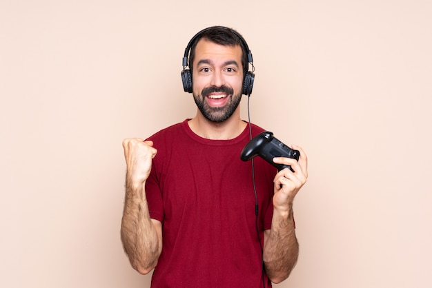 Mężczyzna gra z kontrolerem gier wideo na izolowanej ścianie świętuje zwycięstwo w pozycji zwycięzcy