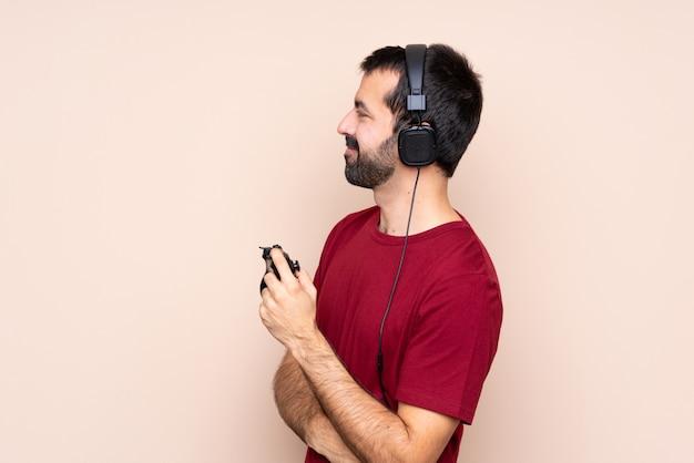 Mężczyzna gra z kontrolerem gier wideo na izolowanej ścianie w pozycji bocznej