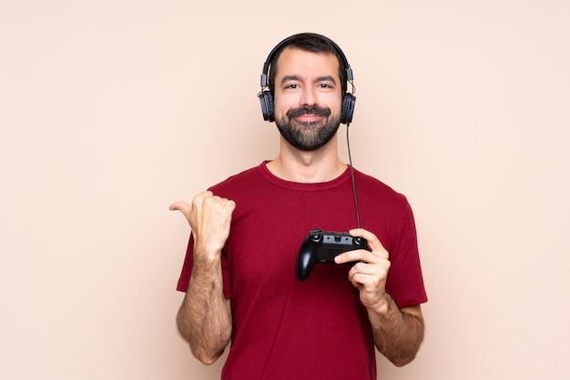 Mężczyzna gra z kontrolerem gier wideo na izolowanej ścianie, wskazując na bok, aby przedstawić produkt