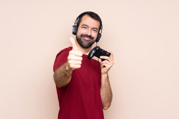 Mężczyzna gra z kontrolerem gier wideo na izolowanej ścianie z kciukami do góry, ponieważ stało się coś dobrego