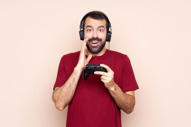 Mężczyzna gra z kontrolerem gier wideo na izolowanej ścianie z zaskoczenia i zszokowany wyraz twarzy