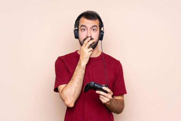 Mężczyzna gra z kontrolerem gier wideo na izolowanej ścianie zaskoczony i zszokowany, patrząc w prawo