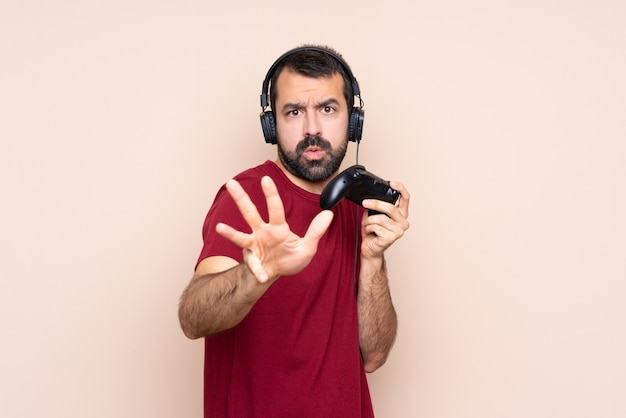 Mężczyzna gra z kontrolerem gier wideo na izolowanych ścianach nerwowe rozciąganie rąk do przodu
