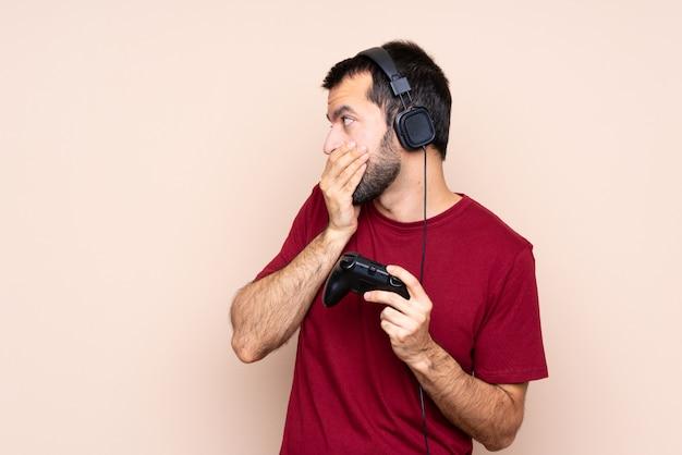 Mężczyzna gra z kontrolerem gier wideo na izolowanych ścianach obejmujących usta i patrząc z boku