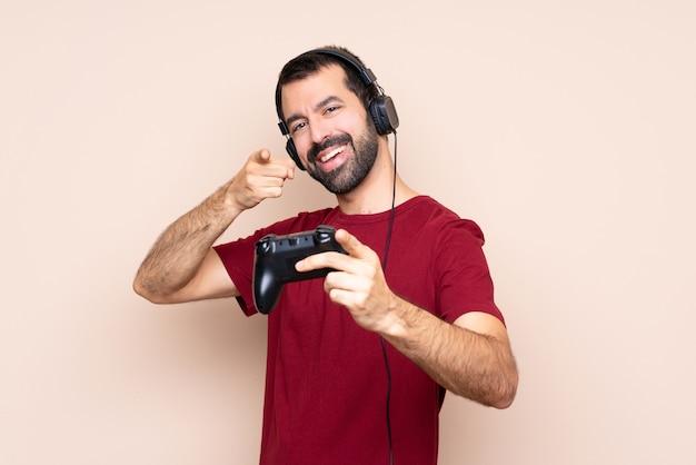 Mężczyzna gra z kontrolerem gier wideo na pojedyncze punkty ściany palcem na ciebie, jednocześnie uśmiechając się
