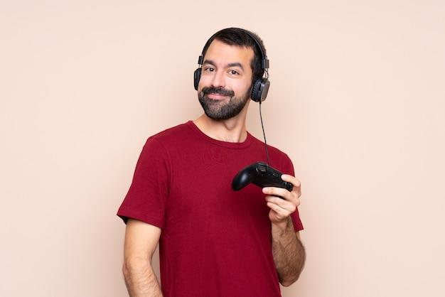 Mężczyzna gra z kontrolerem gier wideo śmiejąc się na białym tle ściany