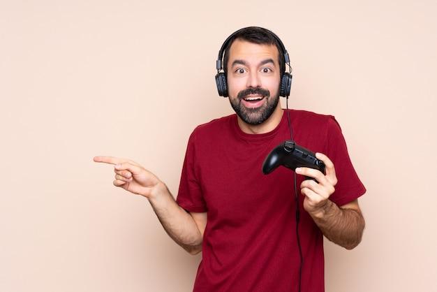 Mężczyzna gra z kontrolerem gier wideo zaskoczony i wskazując palcem na bok