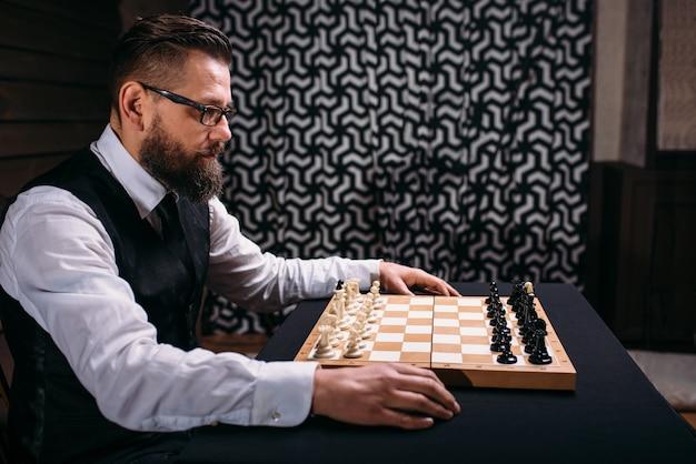 Mężczyzna gracz przeciwko szachownicy z zestawem sztuk