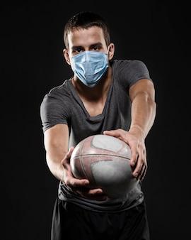 Mężczyzna gracz rugby z medyczną maską trzymając piłkę