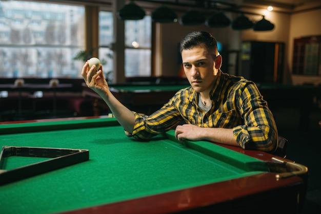 Mężczyzna gracz w bilard trzyma białą piłkę przy stole