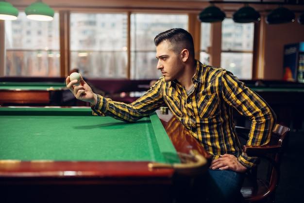 Mężczyzna gracz w bilard trzyma białą piłkę przy zielonym stole. mężczyzna gra w bilard w barze sportowym